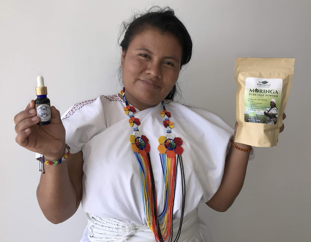 arhuco woman holding nutrasoul moringa oil and powder